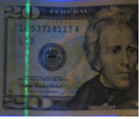 $20 bill glowing green under ultraviolet (UV) light
